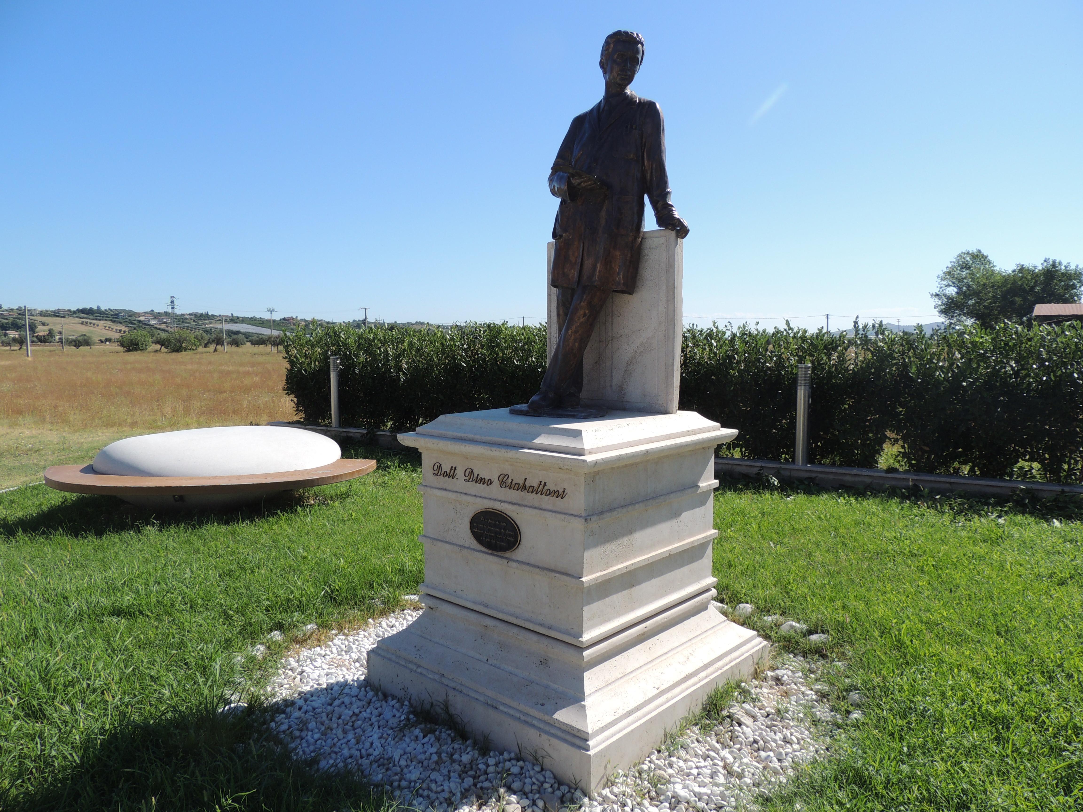 Monumento con base in travertino grezzo anticato, con gole e toro. Statua e targa in bronzo