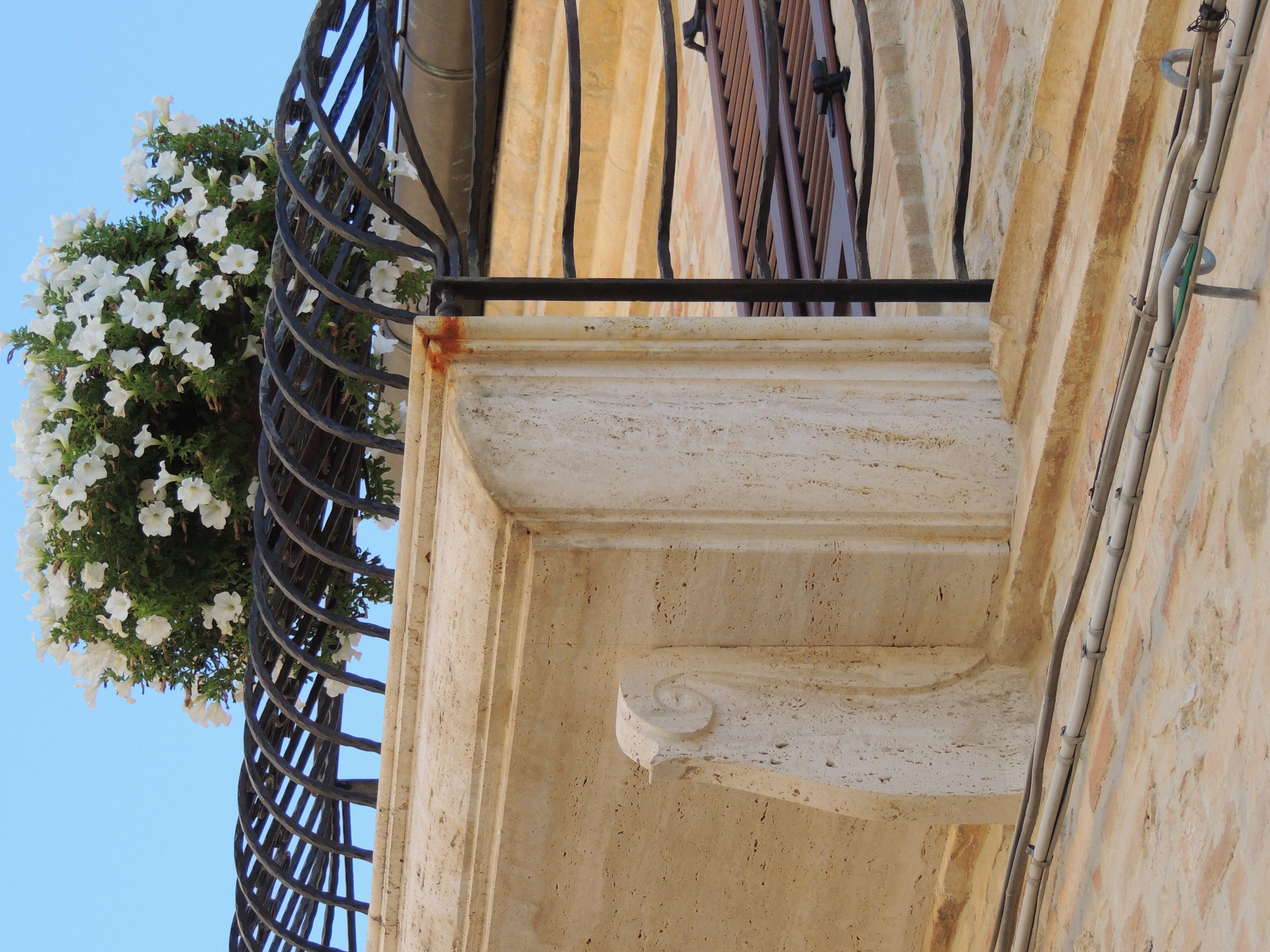 dettaglio balcone in travertino con reggimensola sagomata a mano (progettato e realizzato dall'artigiano).